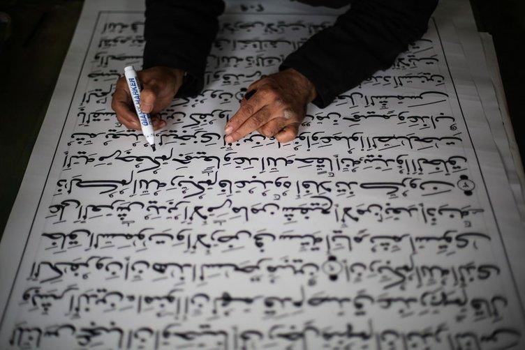 Gazzeli hattat büyük boy Kur'an yazıyor